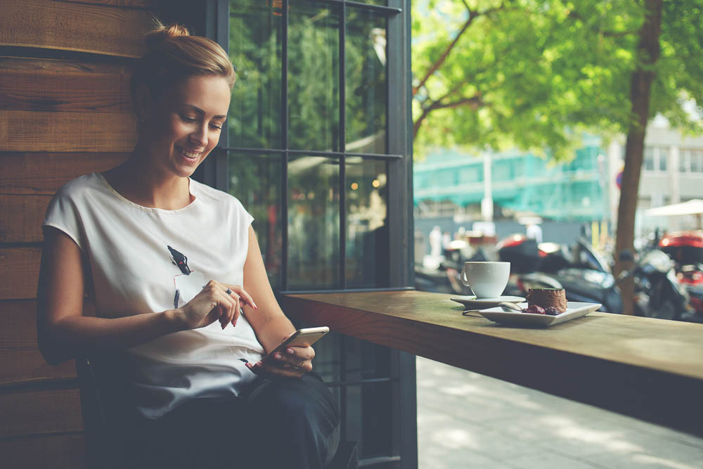 woman with beautiful smile reading good news on mobile phone during rest in coffee shop